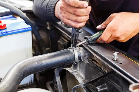 Close up motor vehicle mechanic repairing car radiator, automotive maintenance service