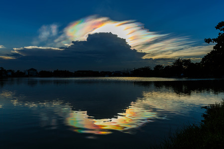 mingled: Colorful iridescent cloud on dark sky in the evening time Stock Photo