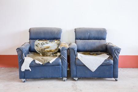 muebles antiguos: sofá de cuero abstracto roto y arruinado pvc sintética en el piso de concreto sucio