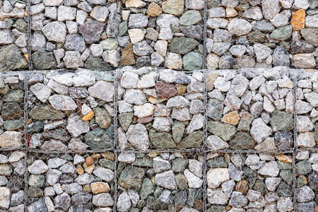 gabion: Stone wall with wire mesh for falling rock protection from mountain Stock Photo