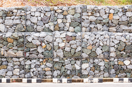 gabion mesh: Stone wall with wire mesh for falling rock protection from mountain Stock Photo