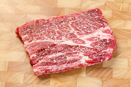 Close up beef chuck steak with sea salt and pepper on wooden chopping board, deep focus image