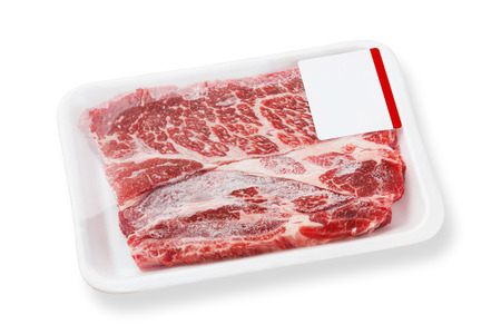 deep focus: Close up beef chuck steak on foam tray with plastic wrapping film and label isolated on white, deep focus image include clipping path