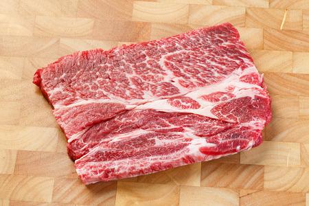 deep focus: Close up beef chuck steak on wooden chopping board, deep focus image