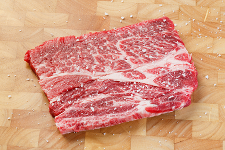 deep focus: Close up beef chuck steak with sea salt on wooden chopping board, deep focus image Stock Photo