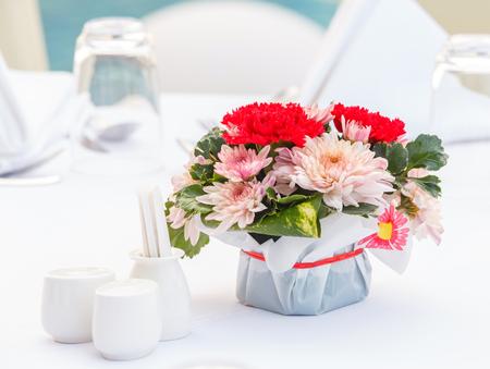 mazzo di fiori: Primo piano crisantemo e fiori garofano bouquet e decorazioni Polyscias foglia su tavolo da pranzo Archivio Fotografico