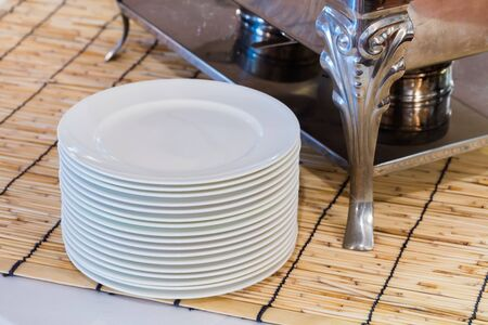 warmer: Stack of white color ceramic dishes beside food warmer