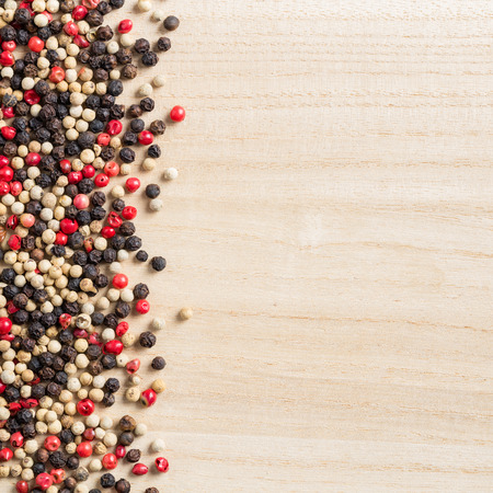 medley: Close up medley trio colorful peppercorn on wooden chopping board background