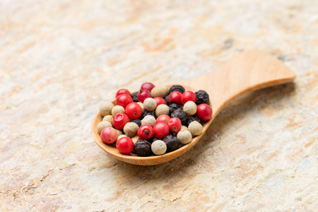 medley: Close up medley trio colorful peppercorn in wooden spoon on stone background