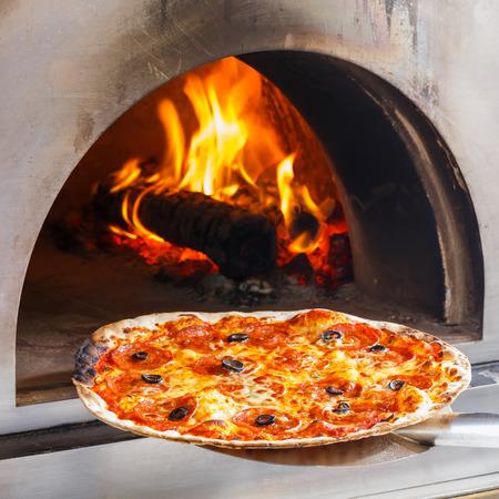 Cierre de la pizza en el horno de leña con la llama detrás
