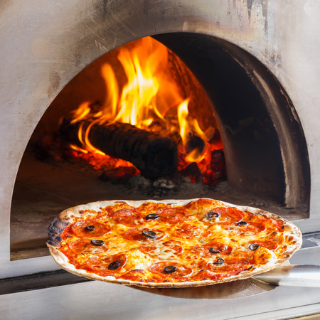 Close up Pizza im Holzofen mit Flamme hinter