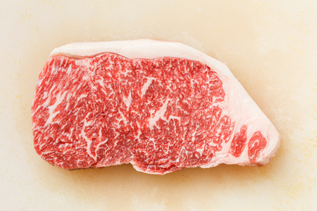 prime: Close up wagyu beef striploin steak on dirty plastic cutting board