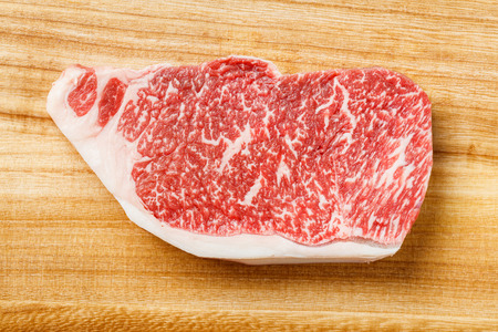 Close up wagyu beef striploin steak on wooden cutting board