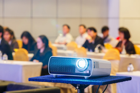 Close up projector in conference room with blurry people background Stock fotó