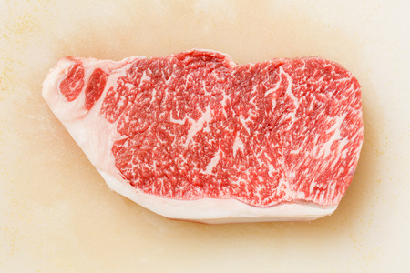 Close up wagyu beef striploin steak on dirty plastic cutting board
