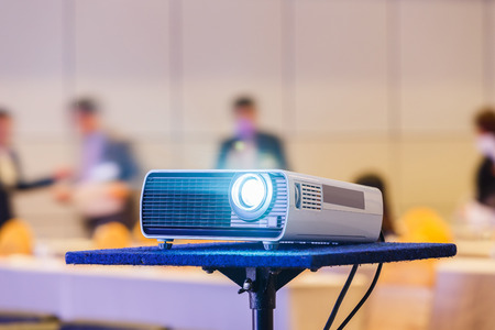 Close up projector in conference room with blurry people background 写真素材