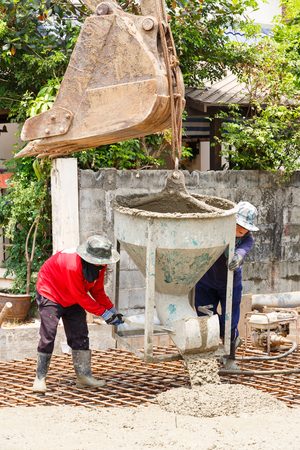 reinforcement: Worker using backhoe to lift concrete bucket in construction site