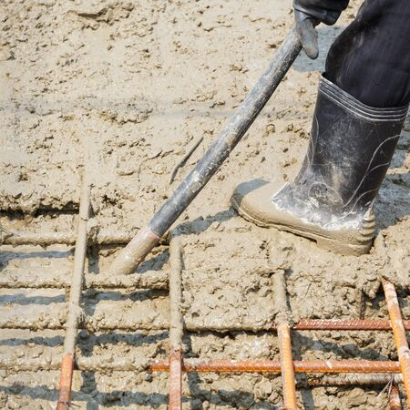 eliminate: Close up worker using concrete vibrator to eliminate voids, increases concrete density and strength
