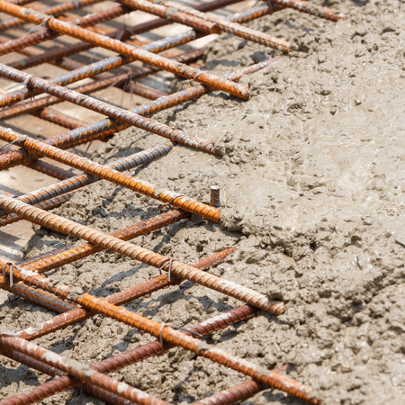 concrete structure: Close up wet cement pour on deformed steel bars with tiewires in construction site, floor pouring
