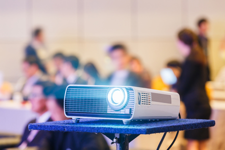 Close up projector in conference room with blurry people background Stock Photo