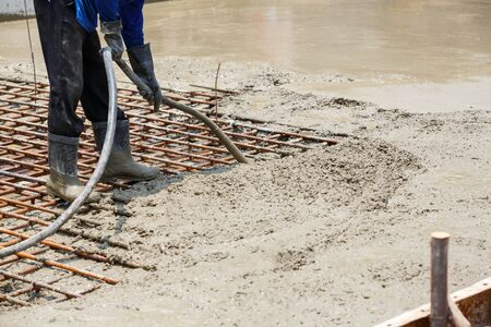 voids: Close up worker using concrete vibrator to eliminate voids, increases concrete density and strength