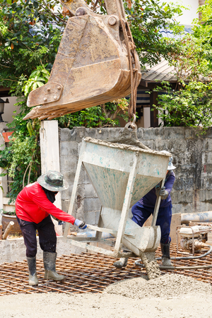 Worker using backhoe to lift concrete bucket in construction site