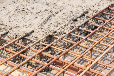 Close up wet cement pour on deformed steel bars with tiewires in construction site, building reinforced concrete floor pouring, rebar reinforcement