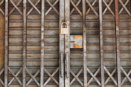 security shutters: Close up dirty padlock on old and rusty steel shutter door Stock Photo