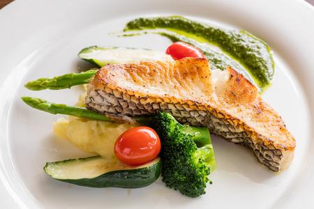 Negro de bacalao filete de pescado servido con pepino, salsa de espinacas, espárragos, tomate, zanahoria, albahaca, puré de patatas Foto de archivo - 69660024