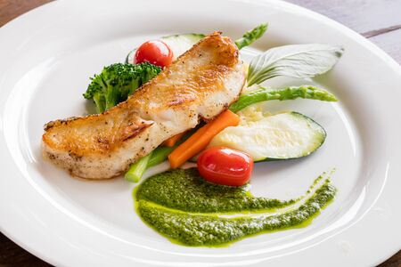 Black cod fish fillet steak served with cucumber, spinach sauce, asparagus, tomato, carrot, basil, mashed  potato