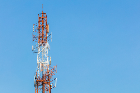 White and red color gsm antenna repeater tower on blue sky, telecommunication concept