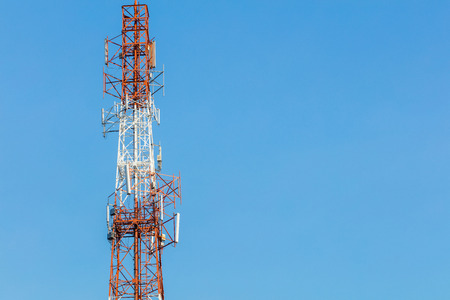 gsm: White and red color gsm antenna repeater tower on blue sky, telecommunication concept