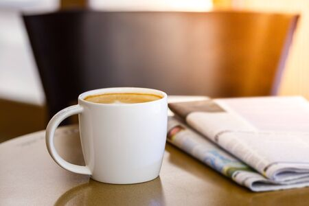 Cappuccino coffee cup on wooden table with newspaper, leisure or business concept
