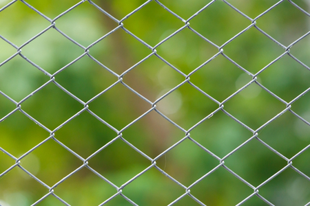Close up old and dirty wire netting fence with green color blur background