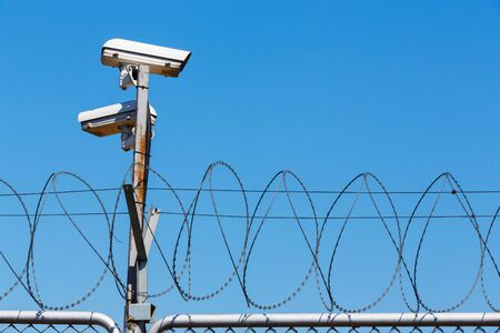 Barbed wire fence with security camera on blue sky, security or forbidden boundary area zone
