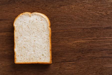 emulsifier: Sliced whole wheat bread on wooden cutting board