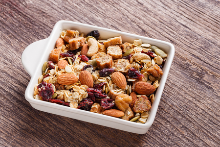 Close up granola or muesli in ceramic bowl on wooden table, dehydrated fruit mix, healthy food, almond, sun dried cultivated banana, cranberry, cashew nut, pumpkin, melon seed Stock Photo