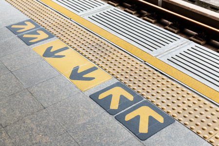 Blind floor tiles with directional arrows sign on train station platform, modern urban lifestyle concept