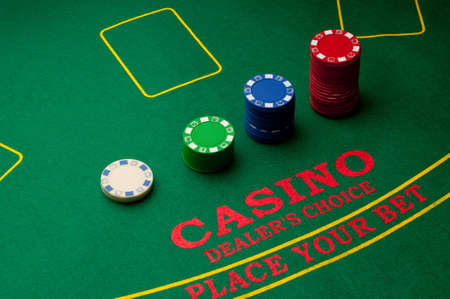 Stack of different coloured chips lined up on a casino table photo