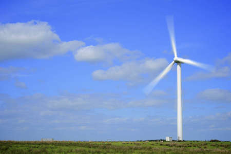Photograph of a wind powered turbine spinning in a green field with beautiful blue sky in the background.  Plenty of space for copy. Stock Photo - 6995333