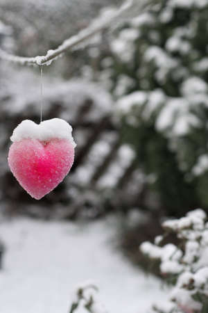 shiver: A photo of a heart shaped ornament hanging from a line and covered in snow Stock Photo