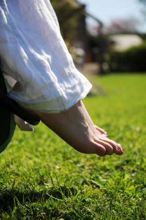 A girls foot dangling down from her chair over some grass on a hot sunny day. photo