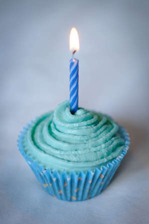Pretty Blue Iced Cupcake for a birthday or celebration with a Blue Candle burning on top  photo