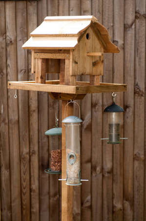 Bird Feeding Table with nuts and seeds hanging from it against a wooden fence photo