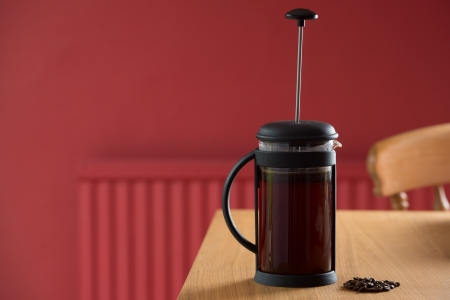 Freshly brewing cafetiere on a kitchen table in a red kitchen with some coffee beans in front of it photo