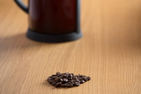 Coffee beans on a wooden table with a freshly brewed cafetiere in the background photo