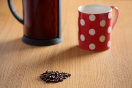 Coffee beans on a wooden table with a freshly brewed cafetiere and red spotty cup in the background photo