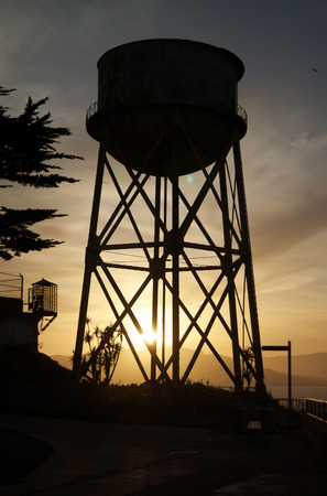 The Sun setting behind the Alcatraz Water Tower in San Francisco Bay, California photo