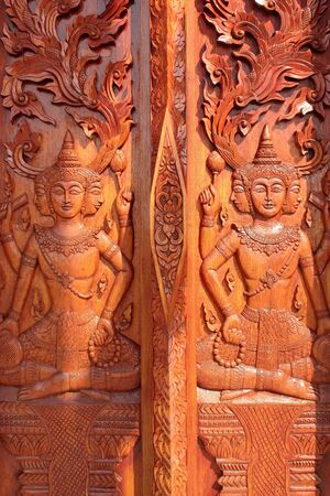 Native Thai style carving, painting on church door in the temple Editorial
