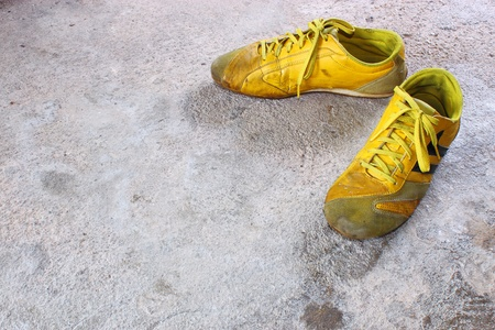 old yellow shoes on concrete photo